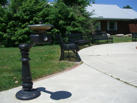 Drinking fountain and benches near paved area of Aldenville Commons